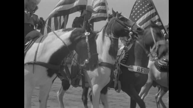 vídeos y material grabado en eventos de stock de interior los angeles coliseum row of cowboys and cowgirls on horseback carry american flags / hi-shot: stadium stands full of audience, infield... - william boyd