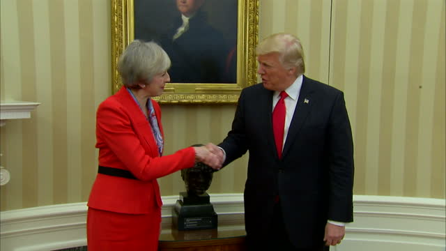 interior mid shot of prime minister theresa may and president donald trump posing together for photo op beside winston churchill bust in oval office... - theresa may stock videos & royalty-free footage