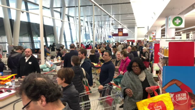 interior of a busy sainsbury supermarket as people panic buy during coronavirus pandemic - queuing stock videos & royalty-free footage