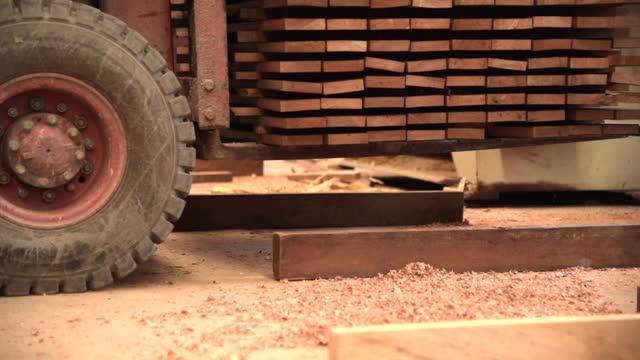 interiör av en växt för träproduktion. fabrik för parkettbräda. vy från lastbil som bär plywood inomhus. stock video - lasta bildbanksvideor och videomaterial från bakom kulisserna