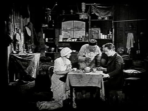vídeos de stock e filmes b-roll de interior of cluttered dilapidated houseboat woman with fancy hat and man wearing suit sit at small table with table cloth while chinese man wearing... - barco casa