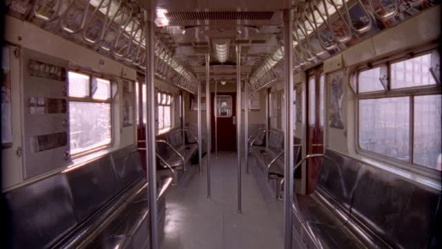 ws interior of empty 7 subway train as it travels above ground/ new york city - pfosten stock-videos und b-roll-filmmaterial