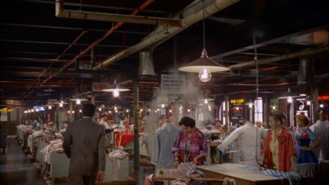 ms td interior of garment factory - anno 1957 video stock e b–roll