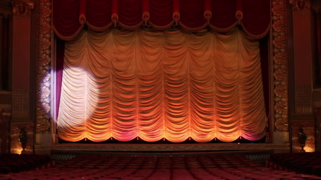 ws interior of historic movie theater, spotlight scans wildly across stage curtain / richmond, virginia, usa - スポットライト点の映像素材/bロール
