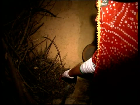 stockvideo's en b-roll-footage met ms interior of house, woman starting a fire, rajasthan, india - hoofdtooi
