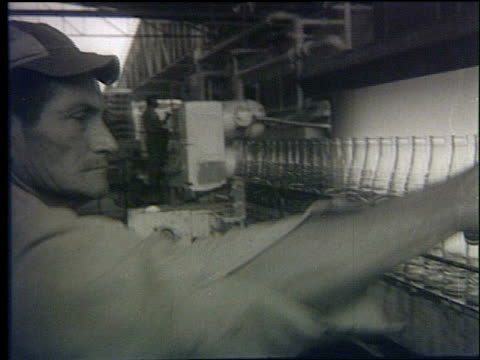 interior of inca kola factory / cola bottles on assembly line / workers moving crates of bottles inca kola plant on october 05 1972 in peru - 1972 stock videos and b-roll footage