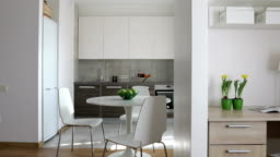 4K. Interior of modern apartment in scandinavian style with kitchen and workplace. Motion panoramic view