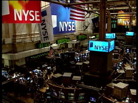 Interior of New York Stock Exchange including monitors electronic ticker tape and traders milling around