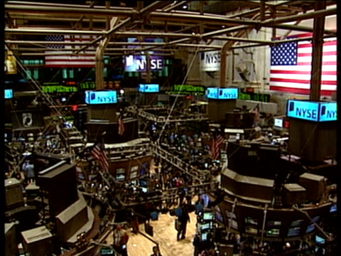 Interior of New York Stock Exchange pan left across monitors and screens with electronic ticker-tape in background traders mill around below