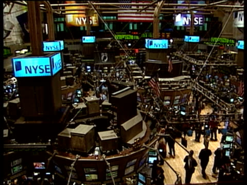 Interior of New York Stock Exchange traders mill around monitors and screens electronic ticker tape in background
