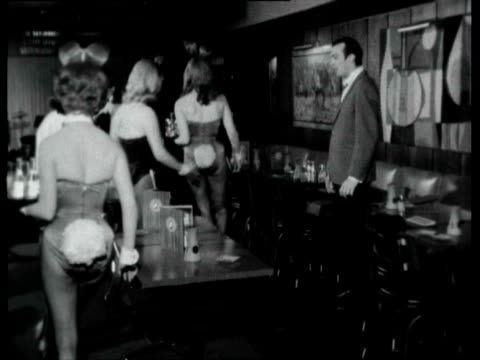 interior of playboy club / women wearing bunny costumes carrying trays of drinks around nightclub during training as man gives them instructions /... - playboy magazine stock videos & royalty-free footage