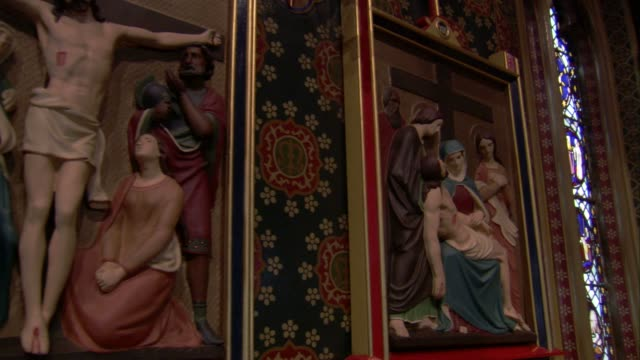 Interior of St Giles Church features stained-glass windows and depictions of Jesus, Cheadle. Available in HD.