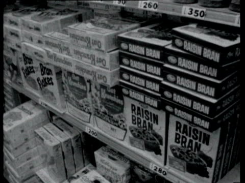 vídeos de stock e filmes b-roll de interior of supermarket / packet of cheese popcorn / signs for candies sweet potato packages post raisin bran flakes and similar breakfast cereals on... - 1964