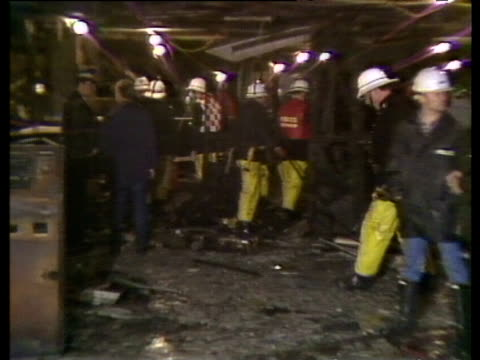 stockvideo's en b-roll-footage met interior of underground station ticket office after fire police and fire crew working debris and water underfoot kings cross underground fire 19 nov... - station london king's cross