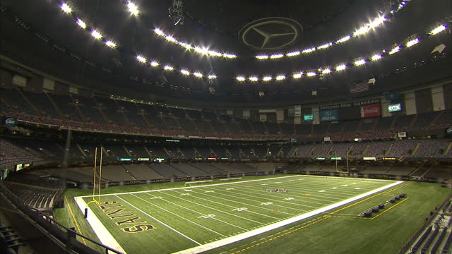 interior pan down and across mercedes benz logo on the ceiling of sports superdome to the empty american football pitch dramatic lights on ceiling on... - mercedes benz stock videos & royalty-free footage