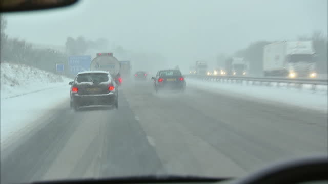 vidéos et rushes de interior point of view shots from car driving on motorway car drives past road sign with delay warning pov motorway driving in snow on january 18... - car point of view
