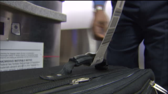 stockvideo's en b-roll-footage met interior point of view shots of a suitcase moving along an airport baggage conveyor and us airways staff attaching baggage security labels onto... - us airways