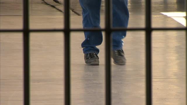 male prisoner legs feet walking down hall toward closed gate barred bars incarceration incarcerated not jail correctional facility - louisiana video stock e b–roll