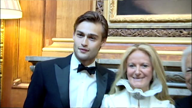Interior shot Douglas Booth model posing for photographs with Ralph Lauren and Ricky Anne LoewBeer at gala dinner hosted by Prince William on May 13...