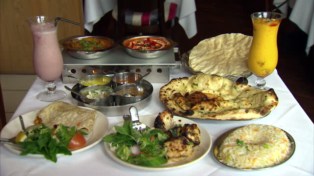 Interior shot Indian meal for two on table with naan chicken chutneys poppadums and lassi drink Indian Meal For Two In Restaurant on July 04 2013 in...
