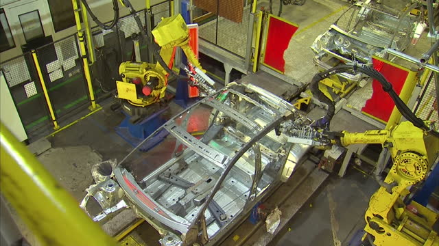 interior shot industrial robots building cars as they move along the production line at the vauxhall assembly plant on january 21 2016 in ellesmere... - autofabrik stock-videos und b-roll-filmmaterial