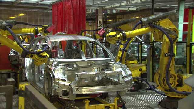interior shot industrial robots building cars as they move along the production line at the vauxhall assembly plant. on january 21, 2016 in ellesmere... - car plant stock videos & royalty-free footage