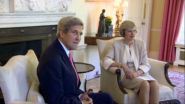Interior shot John Kerry Senator of State and Prime Minister Theresa May sitting together for photo op Kerry says something like 'Are you getting a...