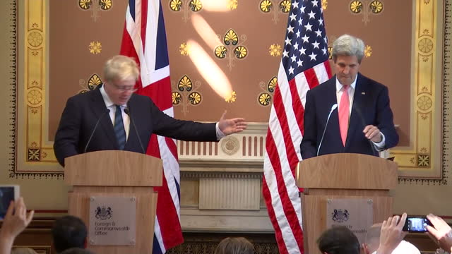 Interior shot John Kerry US Secretary of State and Boris Johnson Foreign Secretary walk in to presser stand behind podium