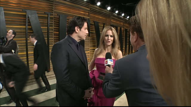 Interior shot John Travolta and wife Kelly Preston being interviewed by a reporter on March 02 2014 in Los Angeles California