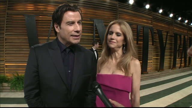 interior shot john travolta wife kelly preston being interviewed by sky reporter amanda walker on march 02 2014 in los angeles california - kelly preston stock-videos und b-roll-filmmaterial