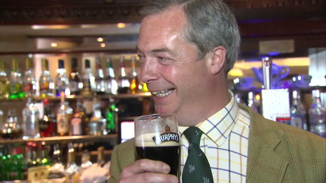 interior shot nigel farage, ukip leader drinking a pint of beer at the europa hotel in belfast and laughing with photographers. on may 14, 2014 in... - pint glass stock videos & royalty-free footage