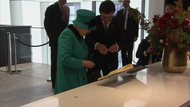 interior shot of queen elizabeth ii signing the guest book at the new schroders headquarters on 7th november 2018 in london, england. - signierstunde stock-videos und b-roll-filmmaterial