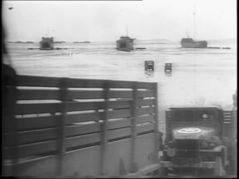 interior shot of supply boat with supplies moving down ramp and onto the beach / wide shot of trucks moving along beach as crane transports supplies... - allied forces stock videos & royalty-free footage
