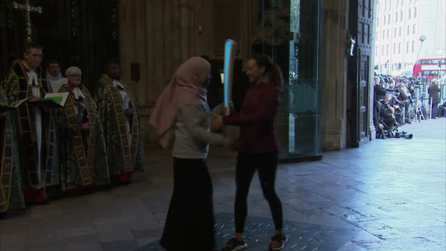 Interior shot Olympic baton carried through Great West Door by Jessica Ennis Hill Olympic gold medalist hugs unknown person other sports figures walk...