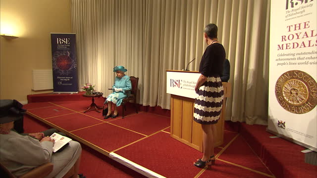 Interior shot Queen Elizabeth II visits the Royal Society of Edinburgh sits during speech presents award medal The medals are awarded for distinction...