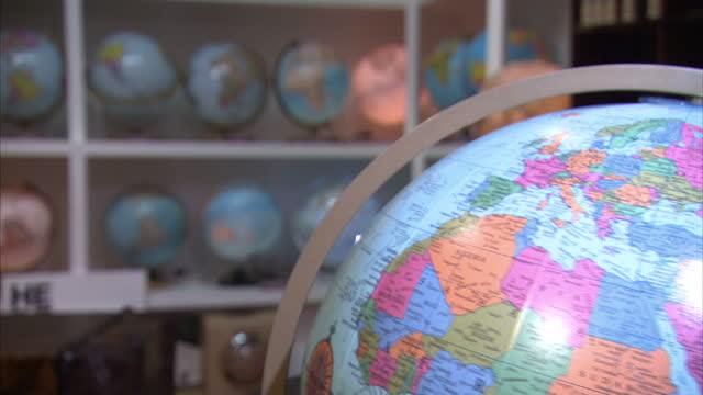 Interior shot spinning Globe slowly turning round and hand spinning it fast Other Globes on shelves in background on January 19 2016 in London England