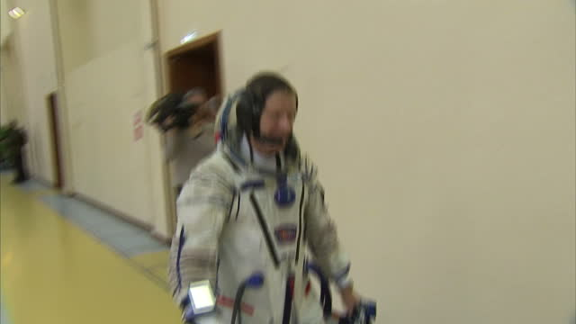 Interior shot Tim Peake walks towards camera wearing space suit