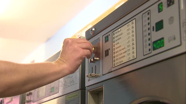 stockvideo's en b-roll-footage met interior shots anonymous mans hand putting coins into washing machine in launderette. on january 26, 2016 in worcester, england. - loterijlootje