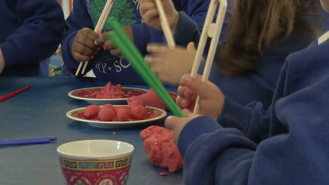 Interior shots anonymous primary school children playing with playdoh in school classroom on in Chiswick England