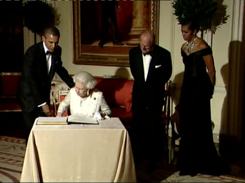 Interior shots Barack Obama the Queen Michelle Obama Prince Philip enter reception area in Winfield House the Queen sits down to sign the visitors...