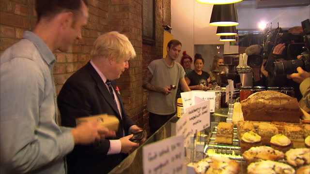 Interior shots Boris Johnson pouring coffee from behind counter gives it to cameraman Boris is give some cakes to take away and departs