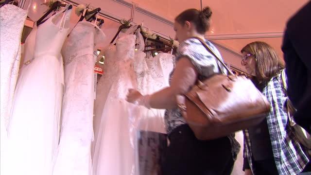 vídeos de stock, filmes e b-roll de interior shots brides to be looking at wedding dresses at the national wedding show at earls court london david cameron says four million couples... - papel em casamento