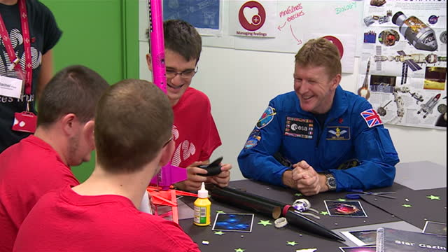 interior shots british astronaut tim peake sitting at table in classroom at the prince's trust bristol centre talking with group of teenagers. on... - プリンスズトラスト点の映像素材/bロール