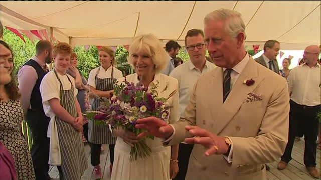 Interior shots Camilla being presented with fresh flowers as Prince Charles shakes hands with the guests workers on July 15 2014 in Axminster England