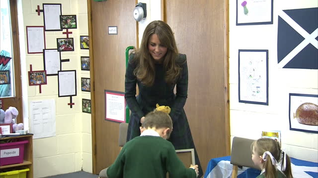 vidéos et rushes de interior shots catherine duchess of cambridge walks to the front of classroom where she is presented by a framed picture a teddy bear by some... - dancing bear