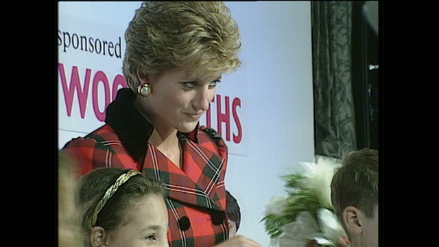 interior shots champion children award ceremony, princess diana is presented an award by nick owen, tv presenter, and stands on stage posing for... - プリンセス点の映像素材/bロール