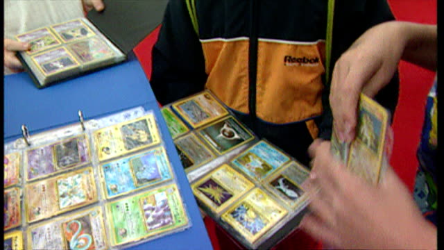 interior shots children comparing pokemon trading cards stored in protective pouches. on september 01, 2000 in london, england. - collection stock videos & royalty-free footage