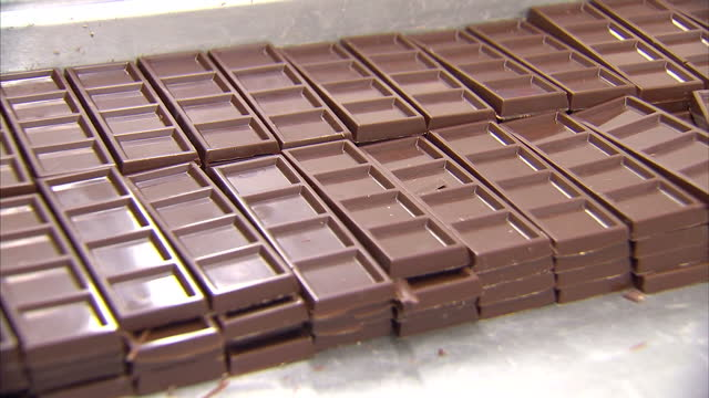 interior shots chocolate bars being stacked fresh out of their molds by moo free chocolates worker on february 05 2015 in reading england - chocolate factory stock videos & royalty-free footage