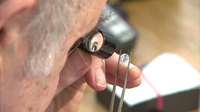 vidéos et rushes de interior shots close of anonymous diamond dealer inspecting diamonds with tweezers & magnifying glass. dealer inspecting diamonds on february 19,... - pince chirurgicale