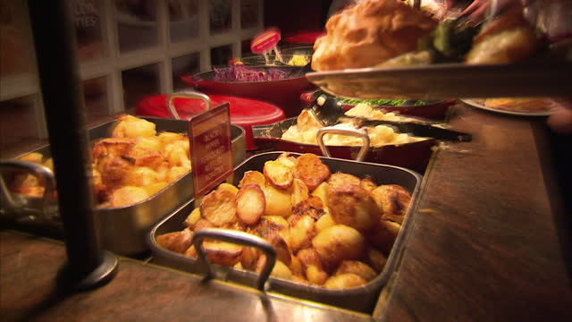 interior shots close ups food including green peas roast potatoes vegetables in carvery self service area interior shots anonymous person piling... - roast dinner stock videos & royalty-free footage
